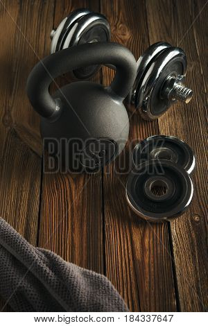 Top View Of Black Iron Kettlebell, Dumbbell And Grey Towel On Wooden Floor Sport Background With Cop