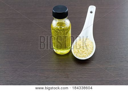 Bottle of sesame oil and sesame seeds in white ceramic spoon on black wooden background