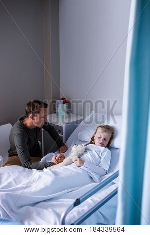Father sitting beside her daughter lying on a bed in hospital
