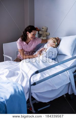 Female doctor consoling patient during visit in ward at hospital