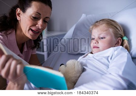 Girl on a bed reading book with her mother in hospital
