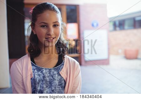 Portrait of happy schoolgirl sitting in school campus