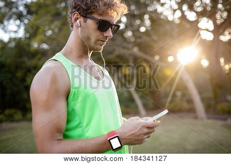 Man listening to music on mobile phone in park