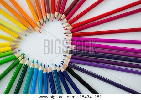 Close-up of colored pencils arranged in heart shape on white background