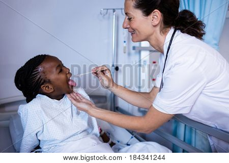 Doctor checking patient fever from thermometer during visit in ward at hospital