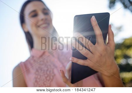 Smiling woman using a digital tablet in the park on a sunny day