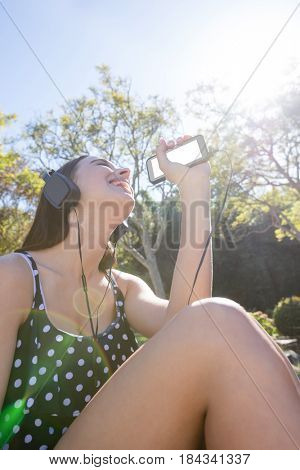 Happy woman listening to music on mobile phone in park