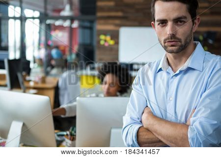 Portrait of a man with arms crossed standing in creative office