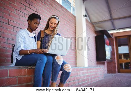 Schoolgirls sitting against brick wall and using laptop in school campus