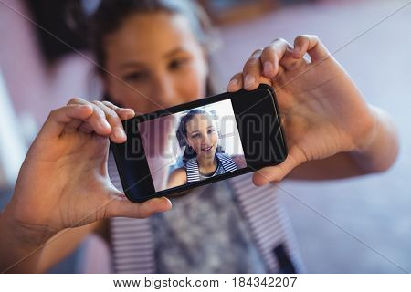 Schoolgirl taking selfie on mobile phone in school campus