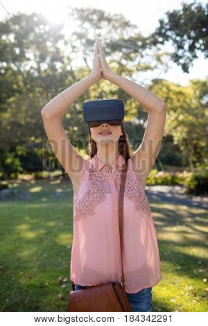 Woman standing with her hands joint while using a VR headset in the park on a sunny day