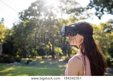 Woman using a VR headset in the park on a sunny day