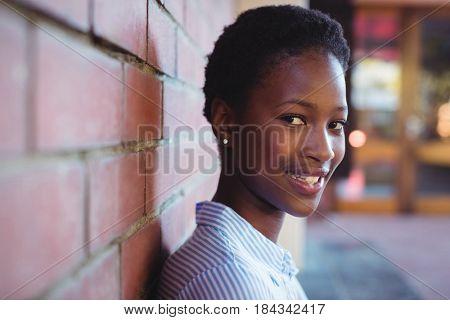 Portrait of happy schoolgirl sitting against brick wall in school campus