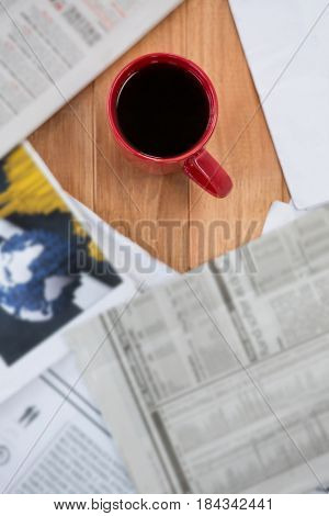 Coffee served in red mug on wooden table