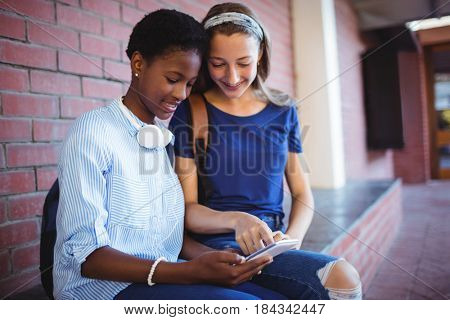 Schoolgirls sitting against brick wall and using mobile phone in school campus