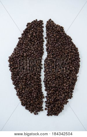 Coffee beans forming coffee bean shape on white background