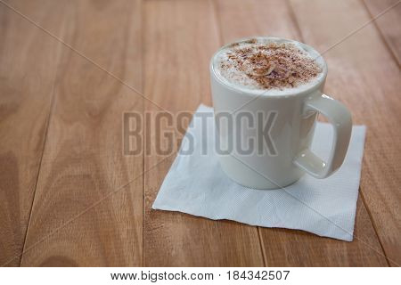 Coffee served in white mug with tissue on wooden table