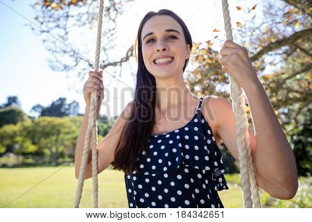 Smiling woman sitting on swing in park on a sunny day