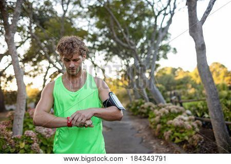 Jogger listening to music on mobile phone and checking his smartwatch in the park