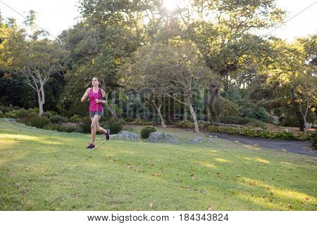 Female jogger listening to music while jogging in the park