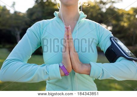 Mid section of female jogger listening to music and exercising with hands joint in the park