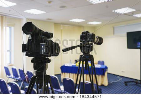 Professional video camera mounted on a tripod to record video during a press conference, an event, a meeting of journalists. Modern technologies, television and video. Soft focus and beautiful bokeh.