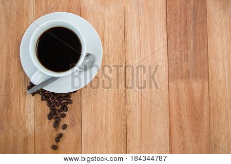 Black coffee with roasted coffee beans on wooden background