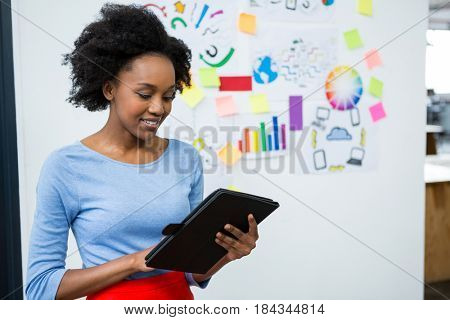 Female graphic designer using graphic tablet in creative office