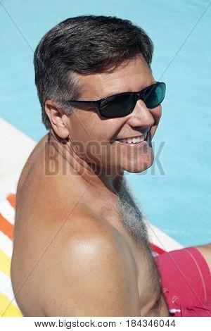 Caucasian man sitting near swimming pool