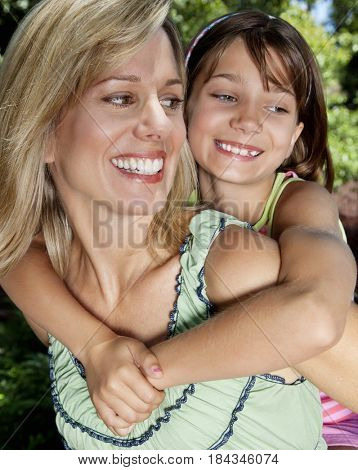 Caucasian mother giving daughter piggyback ride