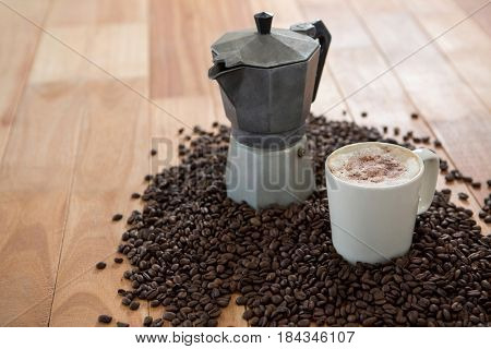 Coffeemaker with coffee beans and coffee mug on wooden table