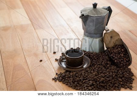 Coffee with coffeemaker and scoop on wooden table