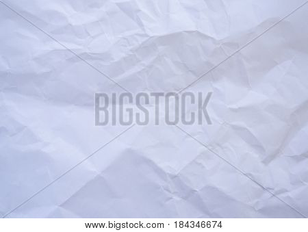 Photo of a crumpled paper. Grunge background with uneven surface. Effect crushed. Empty sheet of paper with space for text.