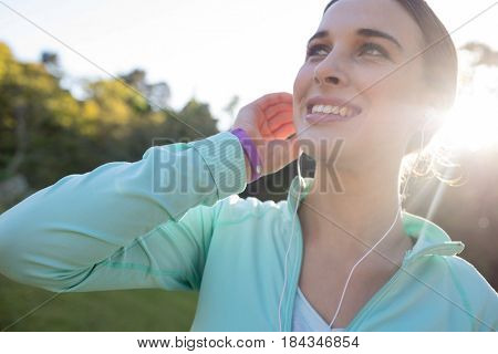 Close-up of smiling female jogger with headphones taking a break from exercise in park
