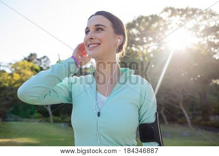 Smiling female jogger with headphones taking a break from exercise in park