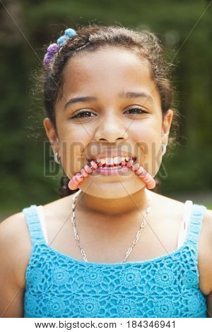 Close up of Hispanic girl biting candy necklace