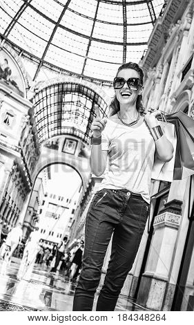 Happy Fashion Woman With Shopping Bags Pointing On Something