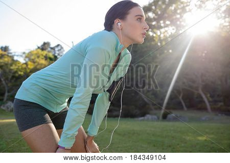 Exhausted female jogger listening to music and leaning on knees while exercising in park