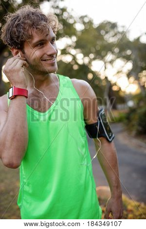 Jogger listening to music on mobile phone in the park