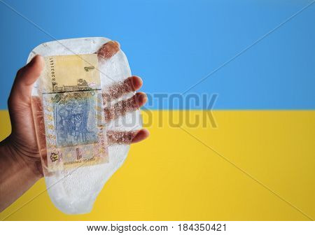 Ukrainian money in ice on a flag background. Devaluation, financial crisis, poverty.