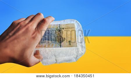 Ukrainian money in ice on a flag background. Devaluation, financial crisis.