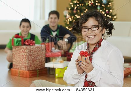Mixed race children sitting with Christmas gifts