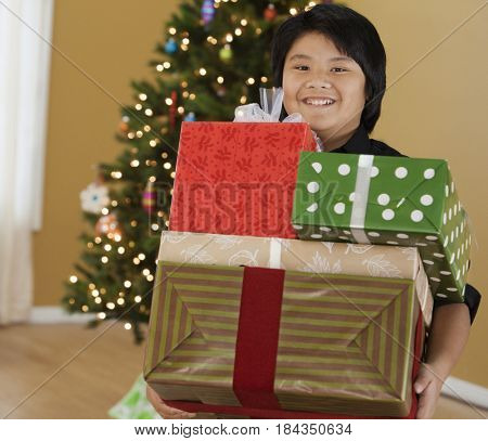 Filipino boy holding stack of Christmas gifts