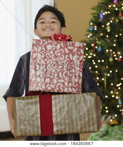 Filipino boy holding Christmas gifts