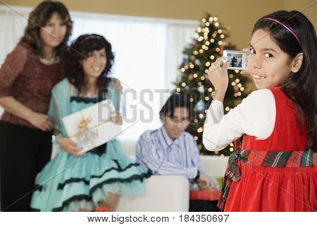 Hispanic girl photographing family at Christmas