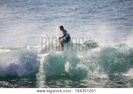 GRAN CANARIA, CANARY ISLANDS - JANUARY 05, 2014: Unidentified man surfing on a large wave on Playa del Ingles on the coast of Atlantic ocean, Gran Canaria, Canary islands, Spain
