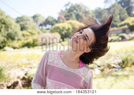 Portrait of woman swaying her hair in park on a sunny day