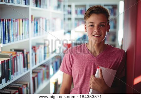 Portrait of happy schoolboy holding book in library at school