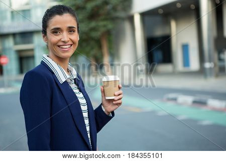 Portrait of business executive holding disposable coffee cup