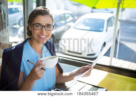 Portrait of female executive looking at document while having coffee at café